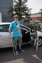 young man on crutches by car